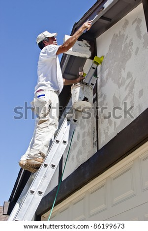 The painter uses a paint roller with brown paint. - stock photo
