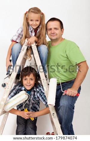 The painters task force - happy kids and their father with painting utensils - stock photo