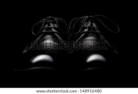The pair of black leather shoes on a black background - stock photo
