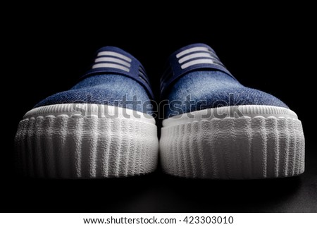 The pair of blue denim sneakers on a black background. - stock photo