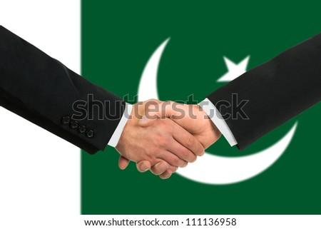 The Pakistani flag and business handshake - stock photo