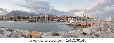 The panorama Marbella city seen from the port, coastal mountain range and cloudy sky are at background, sailing yacht club is at right Costa del Sol, Andalusia, Spain   - stock photo