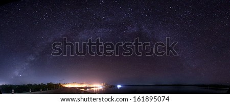 the Panorama Milky Way rises over the dam inThailand. - stock photo