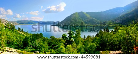 The panorama of a landscape consisting of mountains and lake - stock photo