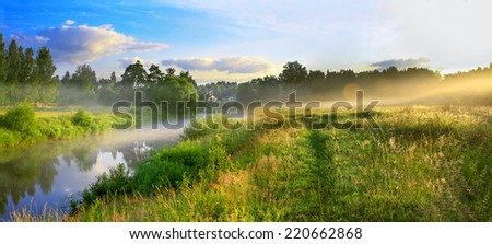 the panorama of a summer landscape with sunrise, fog and the river - stock photo