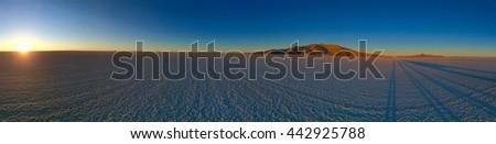 The Panorama of Bolivian Salt Flats with Sun Rising and Moon Setting on the same Horizon. Salar de Uyuni, Bolivia, South America - stock photo