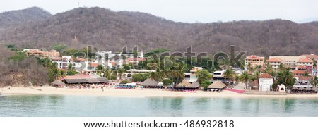 The panoramic view of Bahia de Santa Cruz town beach in early morning (Huatulco, Mexico).
