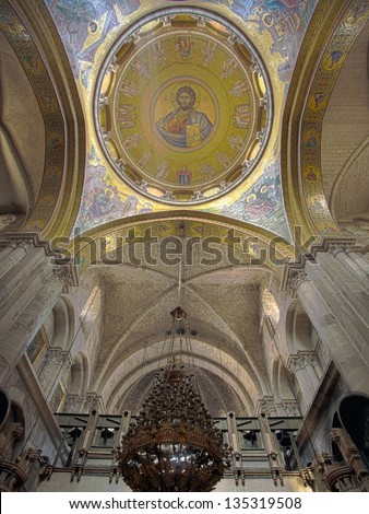 """The """"Pantokrator"""" mosaic in the Basilica of the Holy Sepulchre and the top of the Katholikon beneath it. The old city of Jerusalem, Israel. - stock photo"""