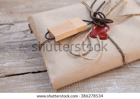The parcel wrapped in Kraft on a wooden background. The gift wrapped in Kraft. Cord and red sealing wax. - stock photo