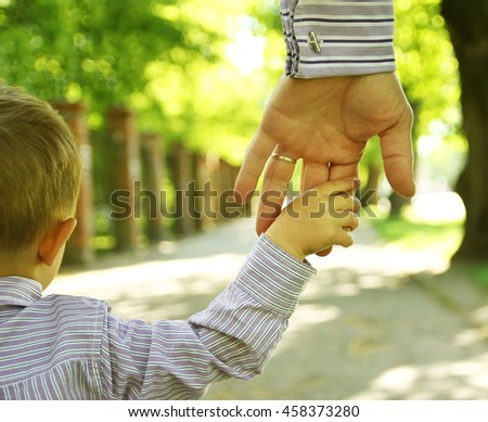 the parent holding the child's hand with a happy background - stock photo