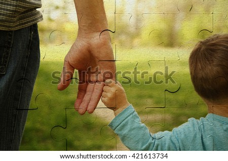 the parent holds the hand of a small child on piece of puzzle - stock photo