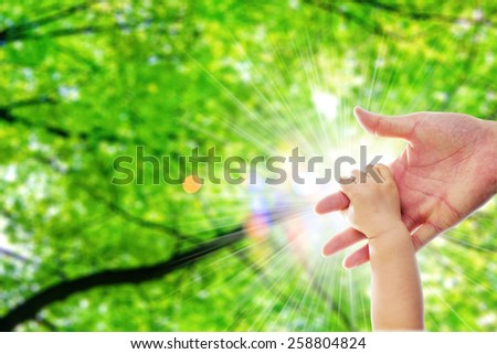 The parent's hand holds on one year old baby's hand behide the nature green tree and blur light close up