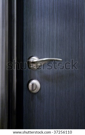 The part of modern wooden closed blue door with handle and lock - stock photo