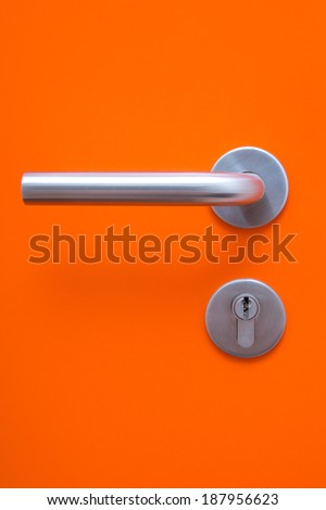 the part of orange door with metal handle and keyhole