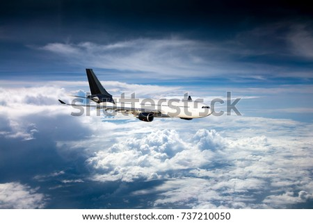 The passenger plane with black tail in flight. Aircraft flies high in the blue sky over clouds.
