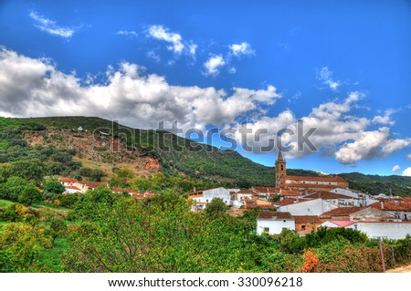 The pastoral village Alajar in southern Spain in HDR. The main church with number of houses on a blue cloudy sky with the background of the mountain