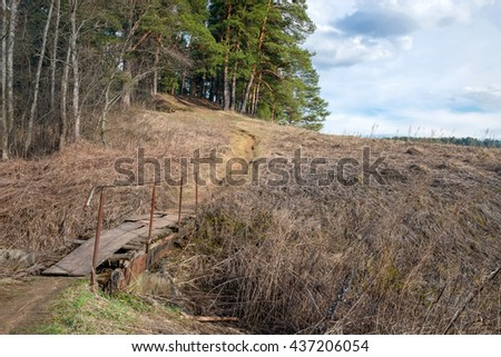The path in the forest through the old iron bridge over a dry creek - stock photo