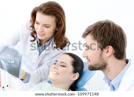 The patient thoroughly examines the x ray photo of her teeth. She is happy that everything is ok - stock photo