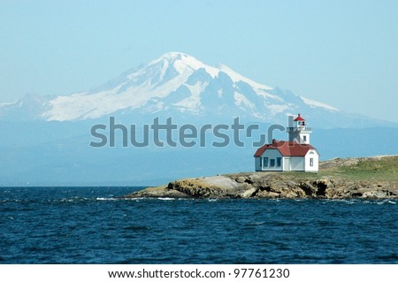 The Patos Island Lighthouse in front of Mt. Baker in Washington's San Juan Islands. - stock photo