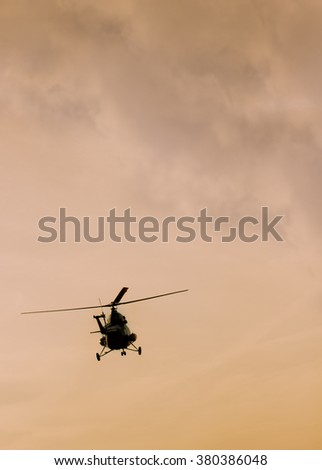The patrol helicopter flying in the sunset sky - stock photo