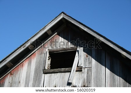 The peak of an old barn set against a blue sky