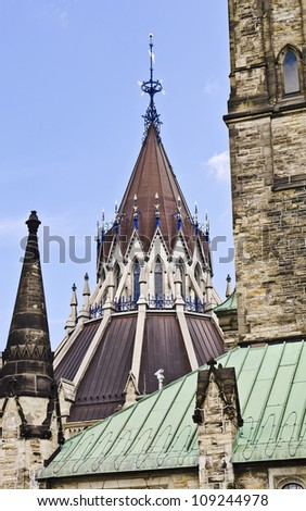 The peak of the Library of Parliament architecture with weathervane, behind the Centre block.
