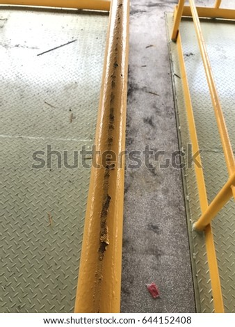 the peel off yellow coating at the handrail. close up image.