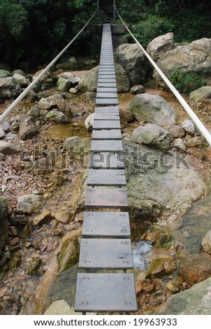 The pendant wood plank bridge with suspension cables over a mountain creek.