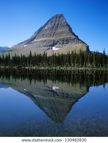 The Perfect Reflection Of A Glacially Carved Peak In A Mountain Lake At Glacier National Park, Hidden Lake, Montana, USA - stock photo