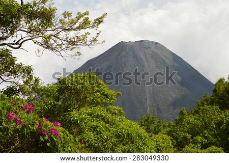 The perfect rocky dusty peak of the active and young Izalco volcano, seen from one of the view points in Cerro Verde National Park near Santa Ana, El Salvador - stock photo
