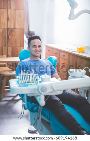 The perfect smile and perfect teeth. The patient dentist sitting in the dental chair waiting for professional consultancy of dentist