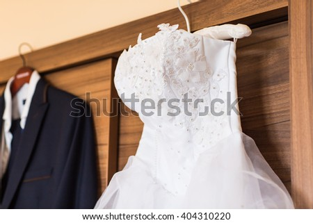 The perfect wedding dress on a hanger in room of  bride  - stock photo