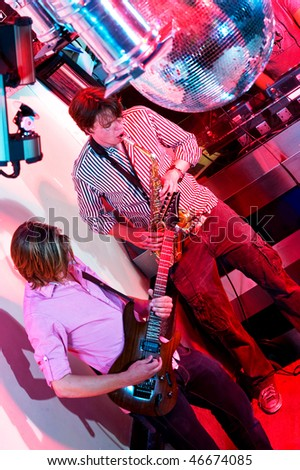 The performance of a saxophonist and a guitarist in a nightclub. - stock photo