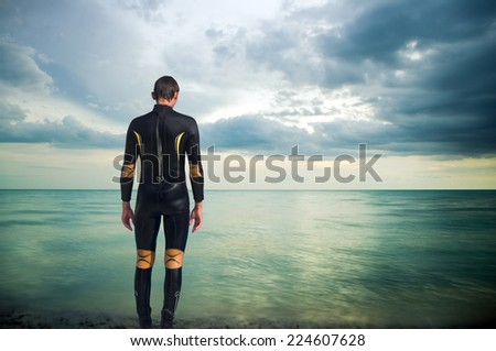 The person in a diving suit on seacoast - stock photo