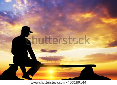 The person sits on a bench against the sunset sky - stock photo