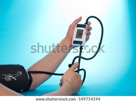 The person supervising a blood pressure by a tonometer, on a blue background