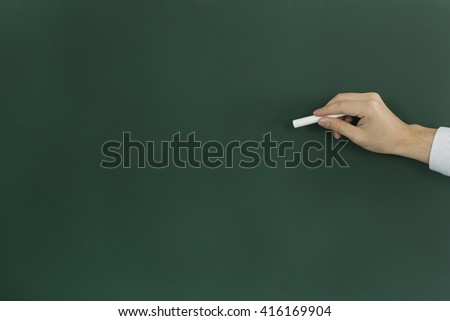 The person who is going to write something on the blackboard with chalk - stock photo