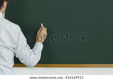 The person who is going to write something on the blackboard with chalk