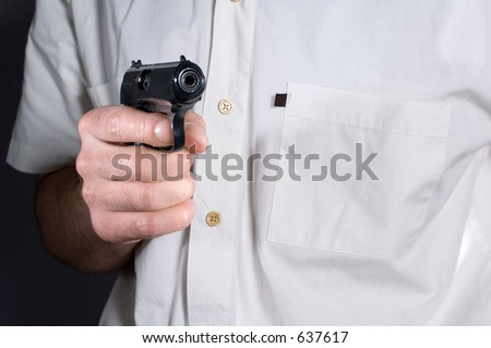 The person with a pistol in position of alertness - stock photo