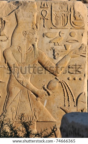 The pharaoh Amenophis III pouring a libation from a ruined piece of masonry at the ancient Egyptian temple of Amun at Karnak, Luxor in Egypt - stock photo
