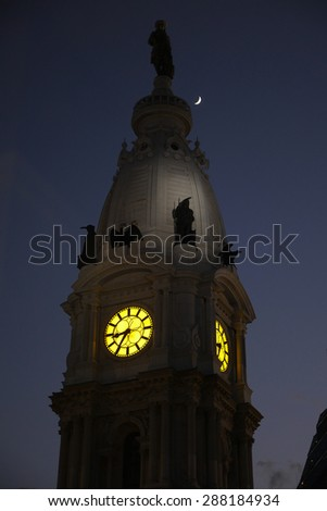 The Philadelphia City Hall clock tower at night with a crescent moon in the sky - stock photo