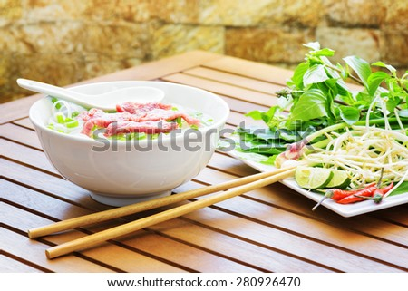 The Pho Bo is a ready to eat on wooden table of street cafe in Vietnam. Traditional Vietnamese food is a beef noodle soup with bean sprouts, red hot chillies, leaves of cilantro and Asian basil. - stock photo