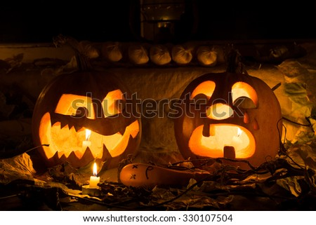 The photo for a holiday Halloween, evil pumpkin sneers at the crying pumpkin.Against an old window with autumn leaves - stock photo