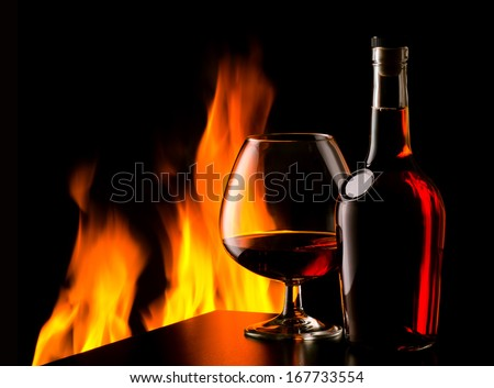 The photo of old cognac on table in front of fireplace - stock photo