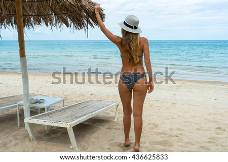 The photo of the beautiful healthy lady in a white hat and black imposing of bikini on a picturesque background of a beautiful view of the sea, looking at the decline sky, a wing,