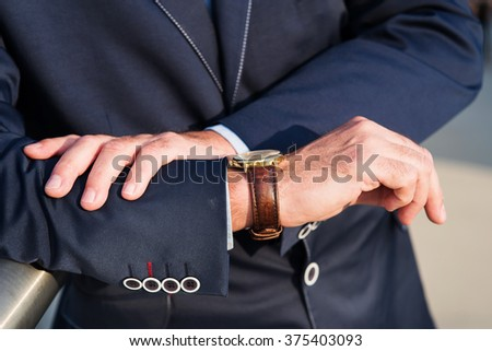 The photo shows a man looking at his watch, which is expected to meet.