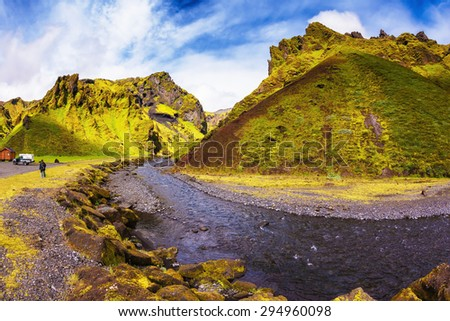 The photo was taken Fisheye lens. Camping in valley of canyon Pakgil. The canyon flowing fast shallow creek. Summer blooming Iceland - stock photo