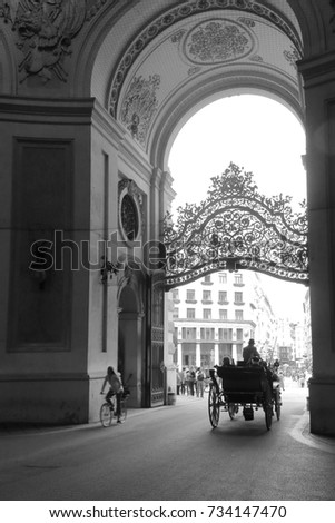 The photo was taken in the city of Vienna. In the photo, the central entrance to the Hofburg Palace. In the driveway you can see a cab.
