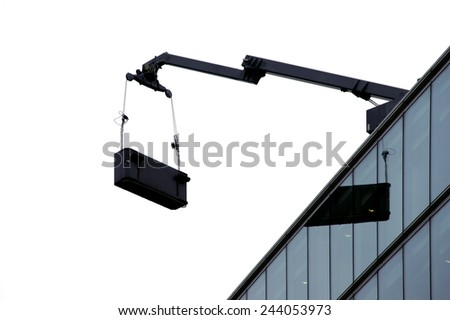 The photograph of a crane arm which is attached to a high-rise building facade / High-rise crane