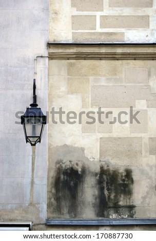 The photograph of a lantern on a prominent wall / Old house wall with lantern